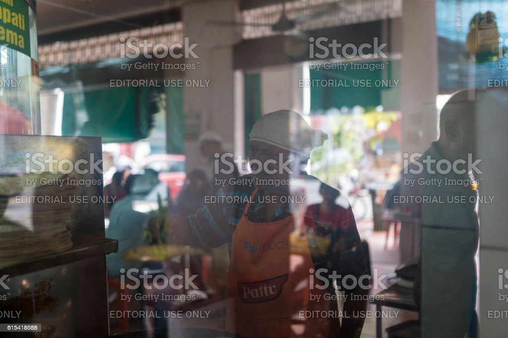 Indian Chef preparing Roti Planta in Coffee Shop, Singapore stock photo