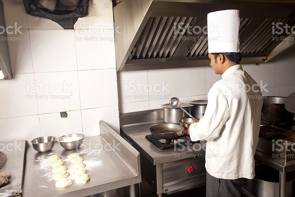 Indian Chef working cooking in a Restaurant Kitchen royalty-free stock photo