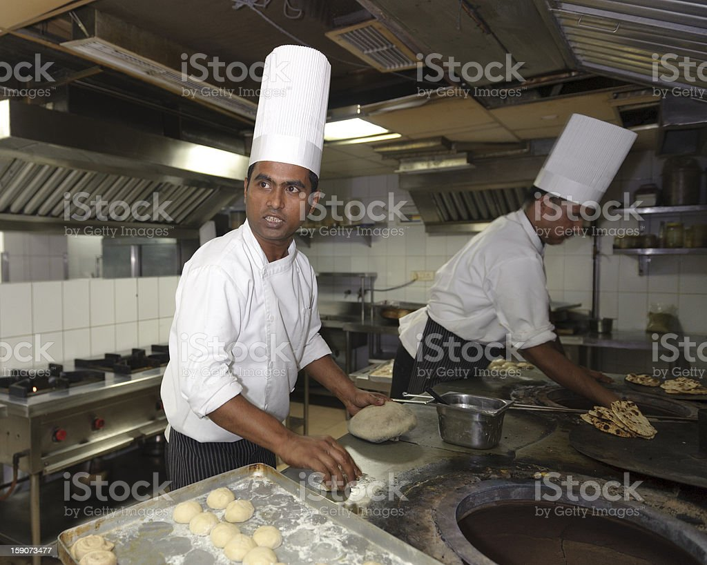 Indian cooks making naan bread stock photo