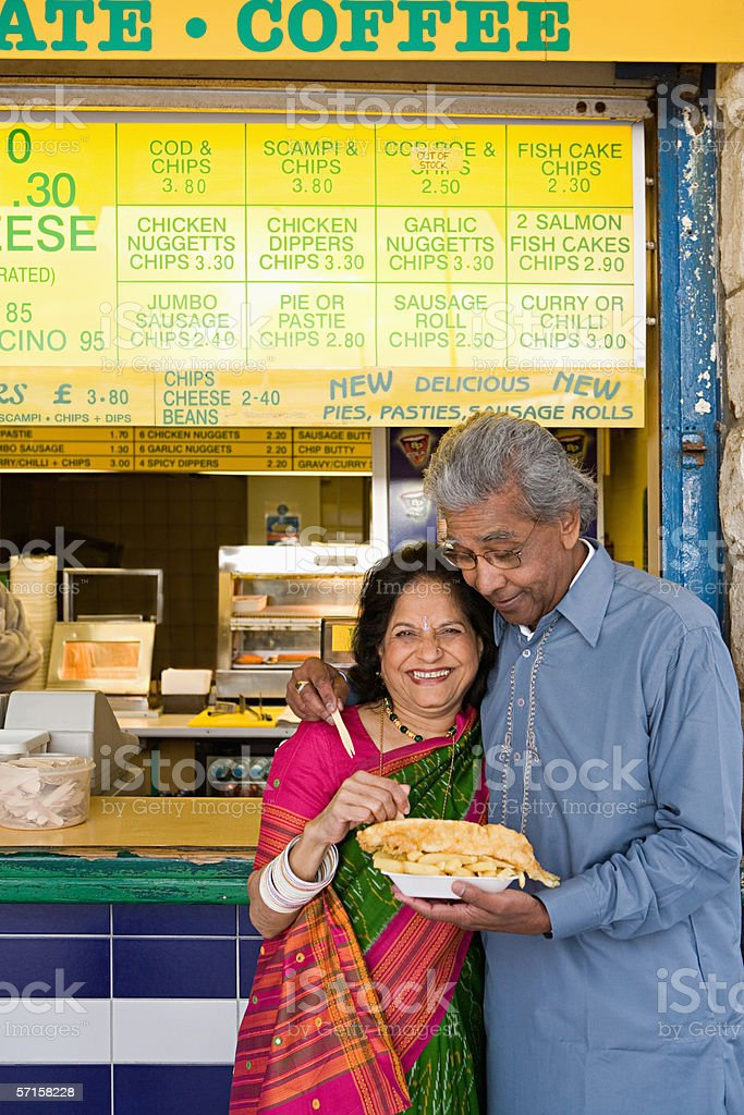 Indian couple having fish and chips stock photo