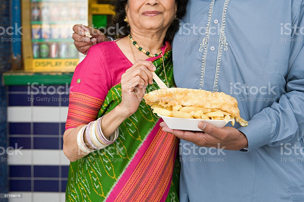 Indian couple with fish and chips stock photo