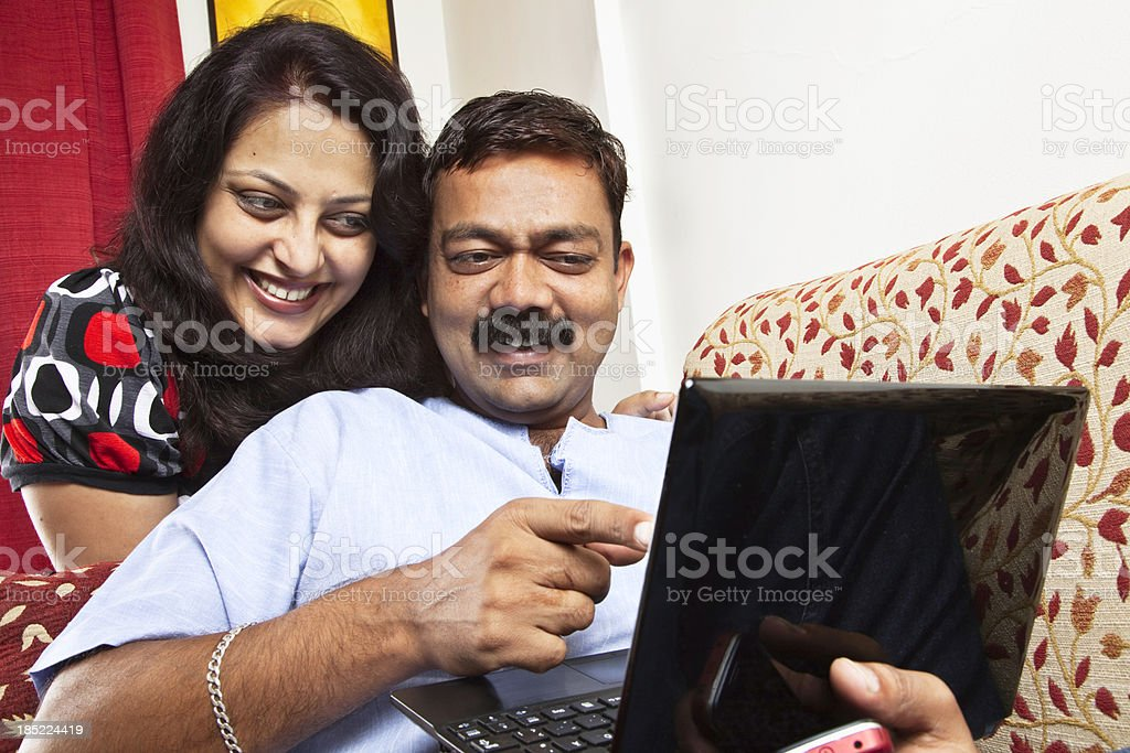 indian couplle with laptop stock photo
