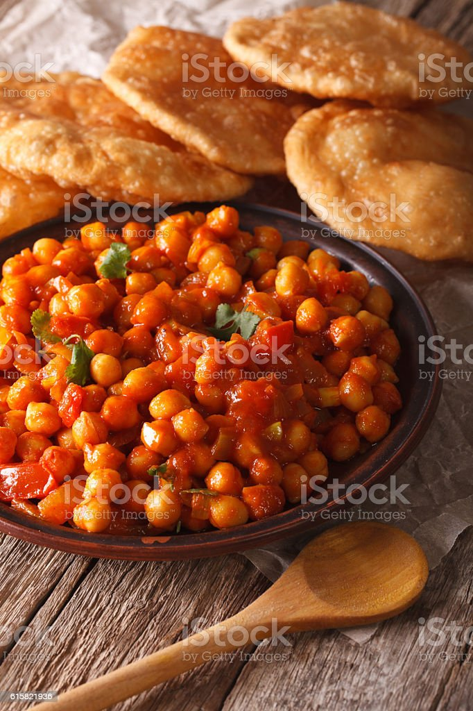 Indian Cuisine: Chana masala and puri bread close-up. Vertical stock photo