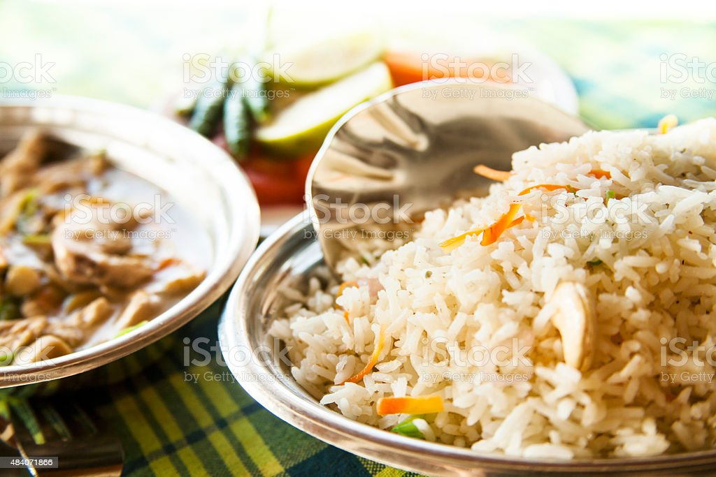 Indian cuisine. Sliced chicken with mushrooms and vegetable biryani. stock photo