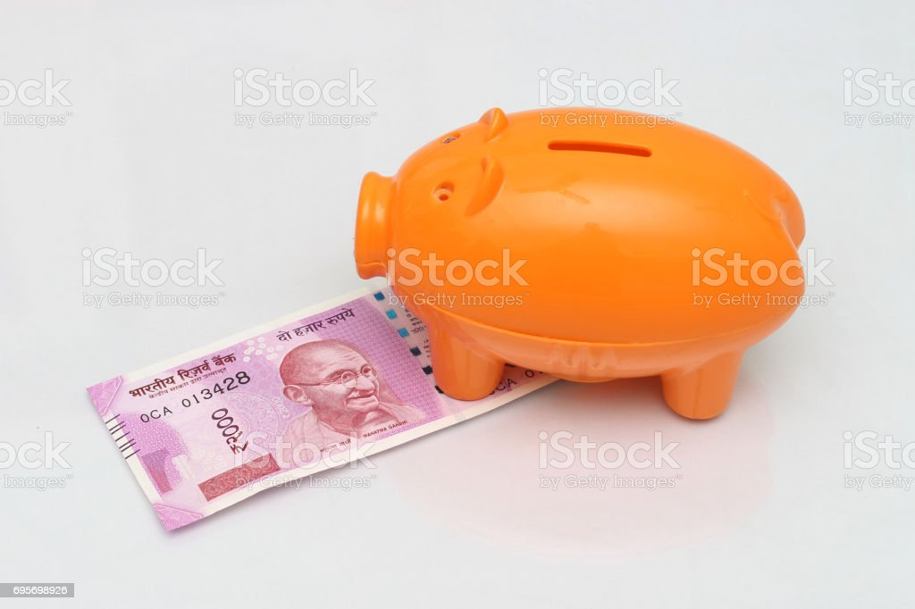 Indian currency with piggy bank. stock photo