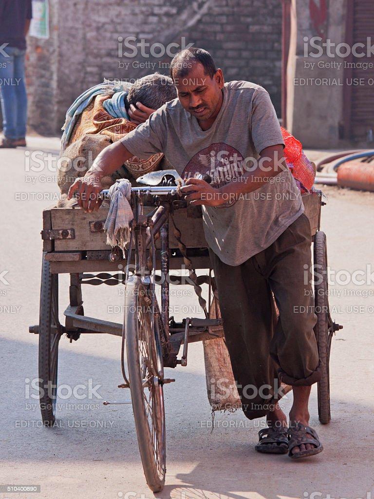 Indian cycle cart driver wheeling a heavy load, Varanasi stock photo