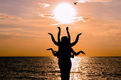Indian dance silhouette on beautiful beach during sunset.
