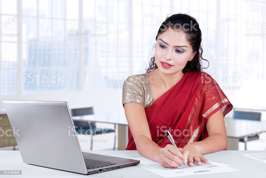 Indian entrepreneur writing document in office stock photo