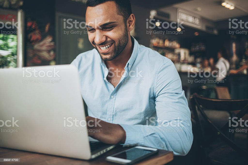 Indian ethnicity man working on laptop in cafe stock photo