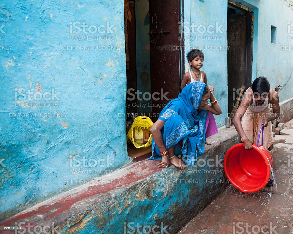 Indian Family Cleaning Washtub In The Street Of Varanasi stock photo
