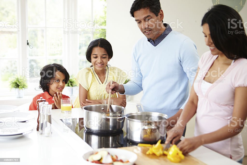 Indian Family Cooking Meal At Home stock photo