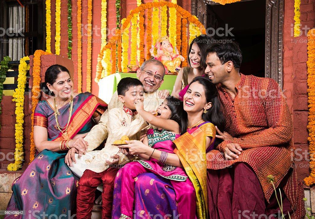 indian family eating sweet laddu on ganesha festival stock photo