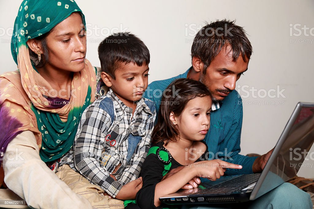 Indian Family Holding Laptop at Home stock photo