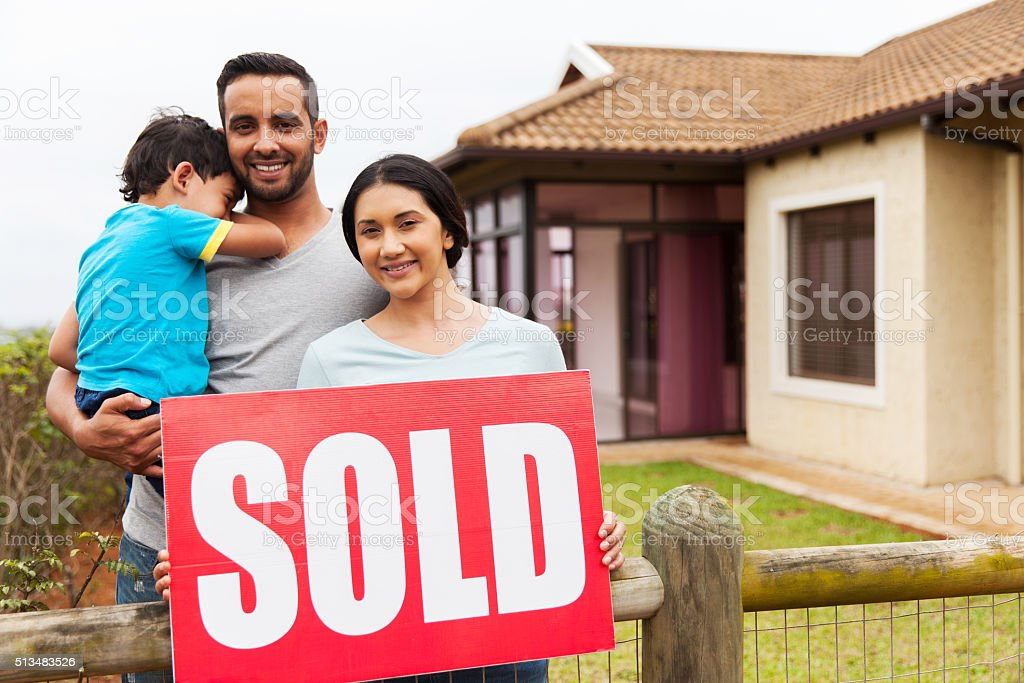 indian family holding sold sign stock photo