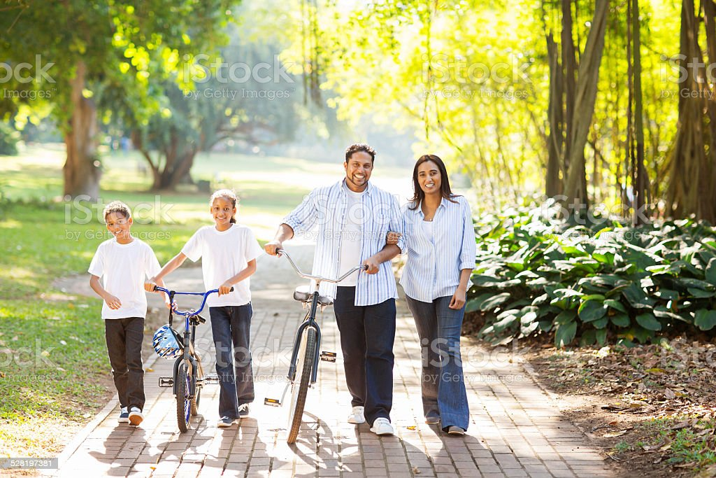 indian family walking outdoors stock photo