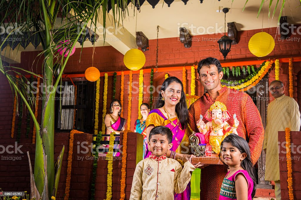 indian family welcoming lord Ganesha idol in ganesha festival stock photo