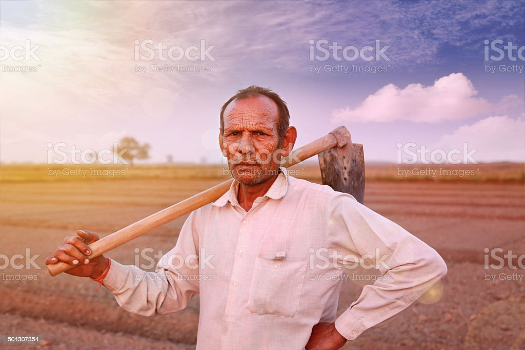 Indian farmer holding hoe on his shoulder stock photo