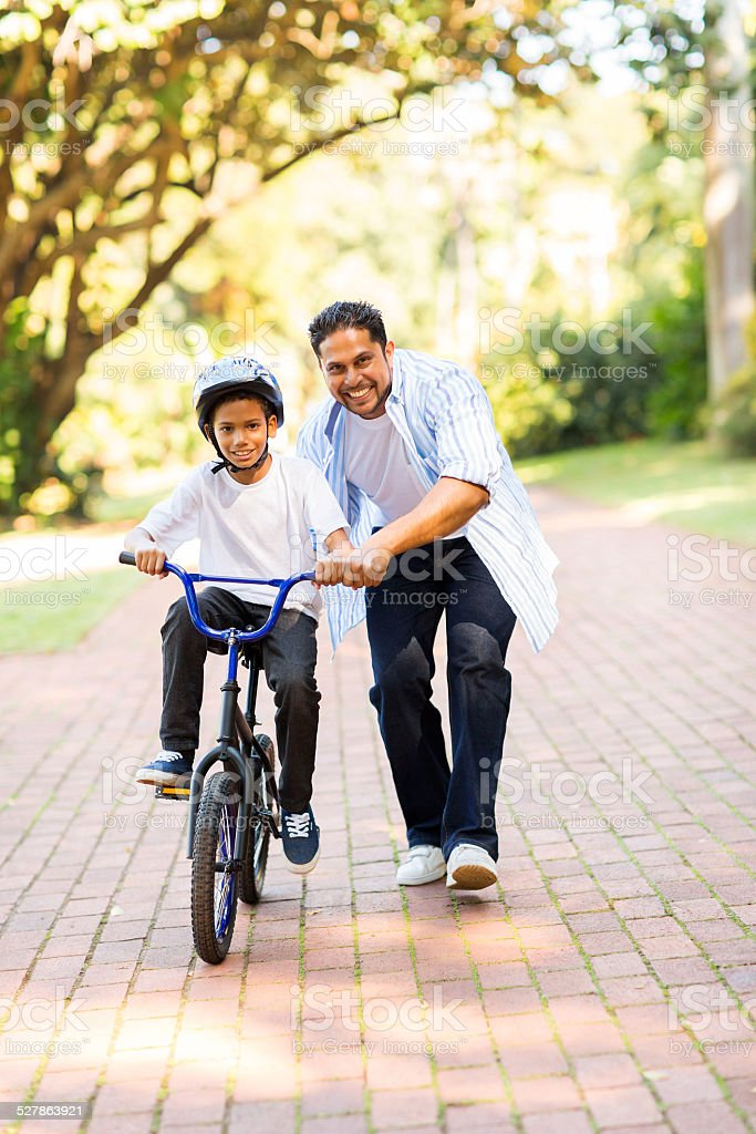 indian father teaching his son to ride a bicycle stock photo