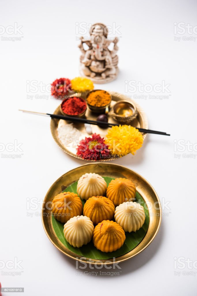 Indian Festival - Indian sweet food called Modak offered as prasad or prashad or chadhava  over green leaf to Lord Ganesha on Ganesh Chaturthi with puja or pooja thali and decorated with flowers stock photo