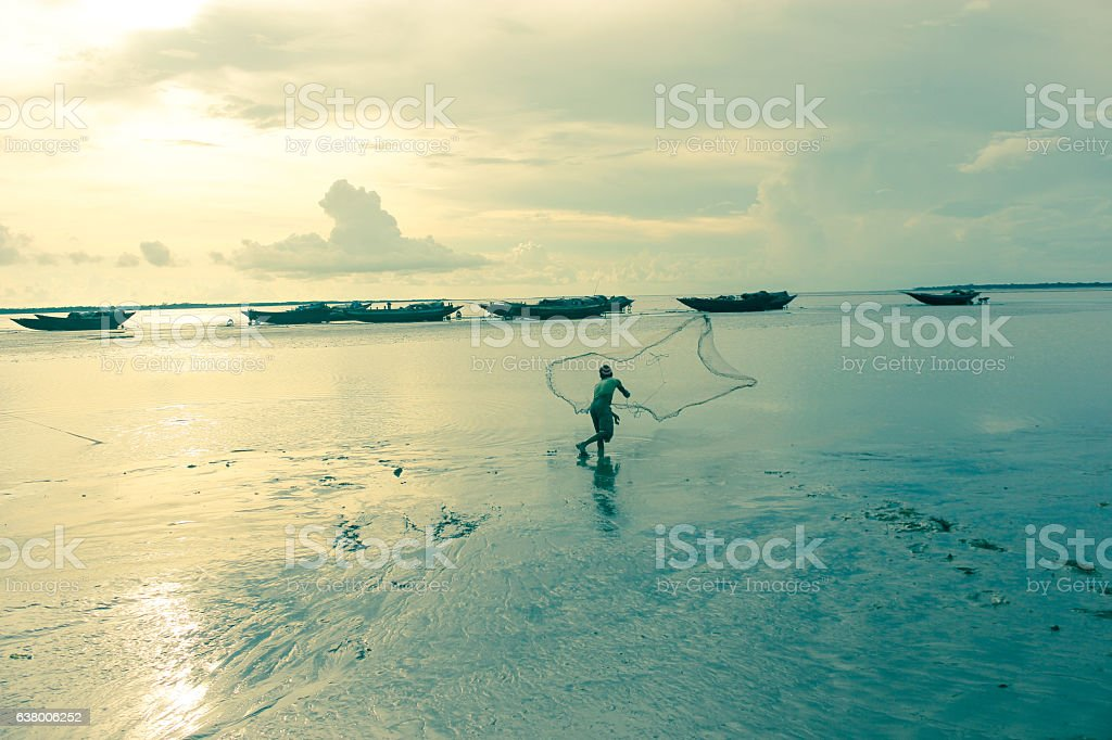 Indian fisherman catch fish during sunset stock photo