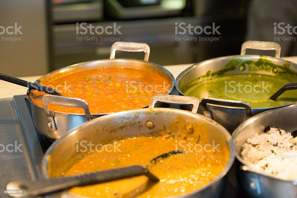 Indian food being kept warm in cooking pans stock photo