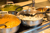 Indian food being kept warm in cooking pans