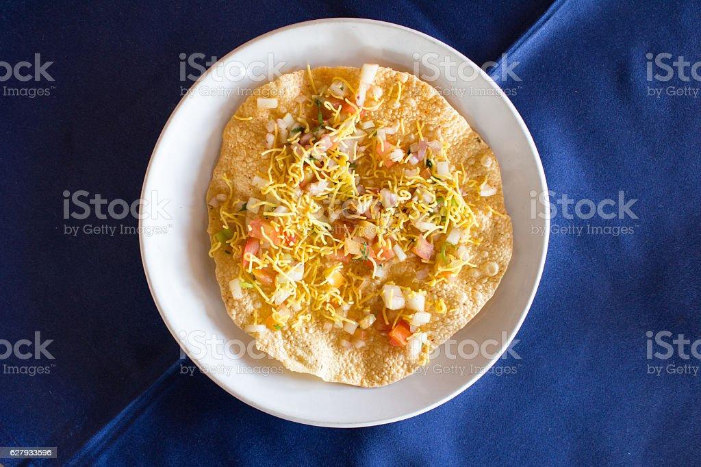 Indian food (Masala papad) on white dish with blue background stock photo