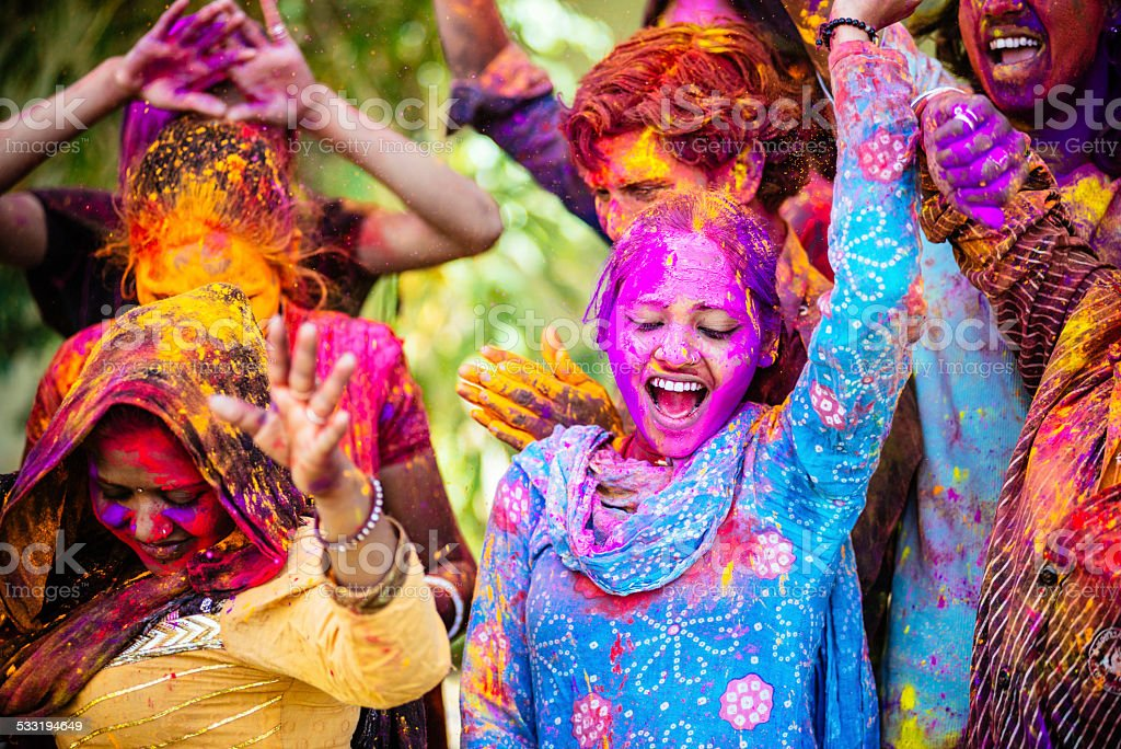 Indian Friends Dancing Covered on Holi colorful powder in India stock photo