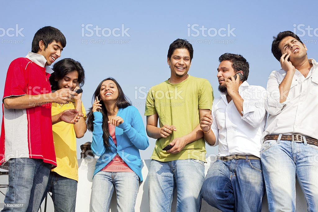 Indian Friends People Talking on cell phones SMS Having Fun royalty-free stock photo