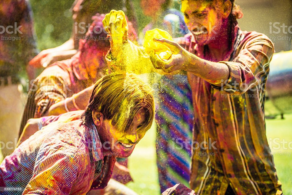 Indian friends throwing Holi Colorful Powder at each other stock photo