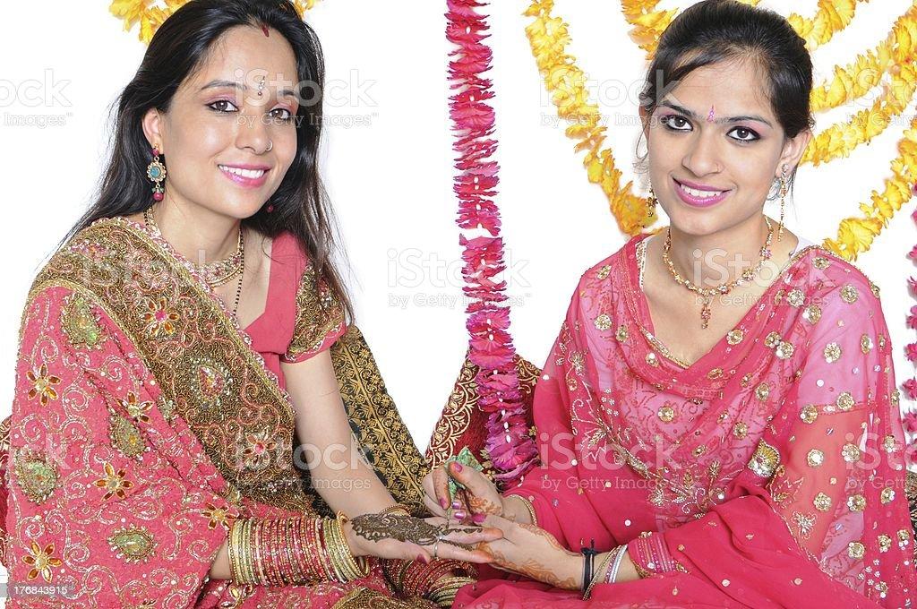 Indian girl applying mehendi on a woman's hand. royalty-free stock photo