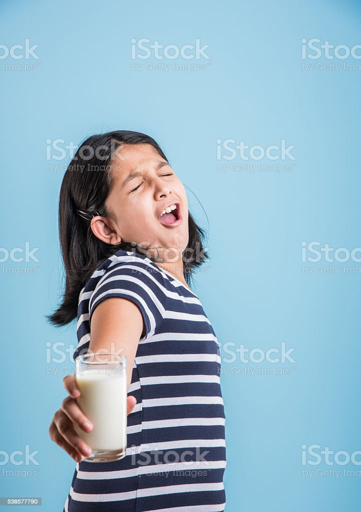 indian girl holding a glass of milk over blue background stock photo