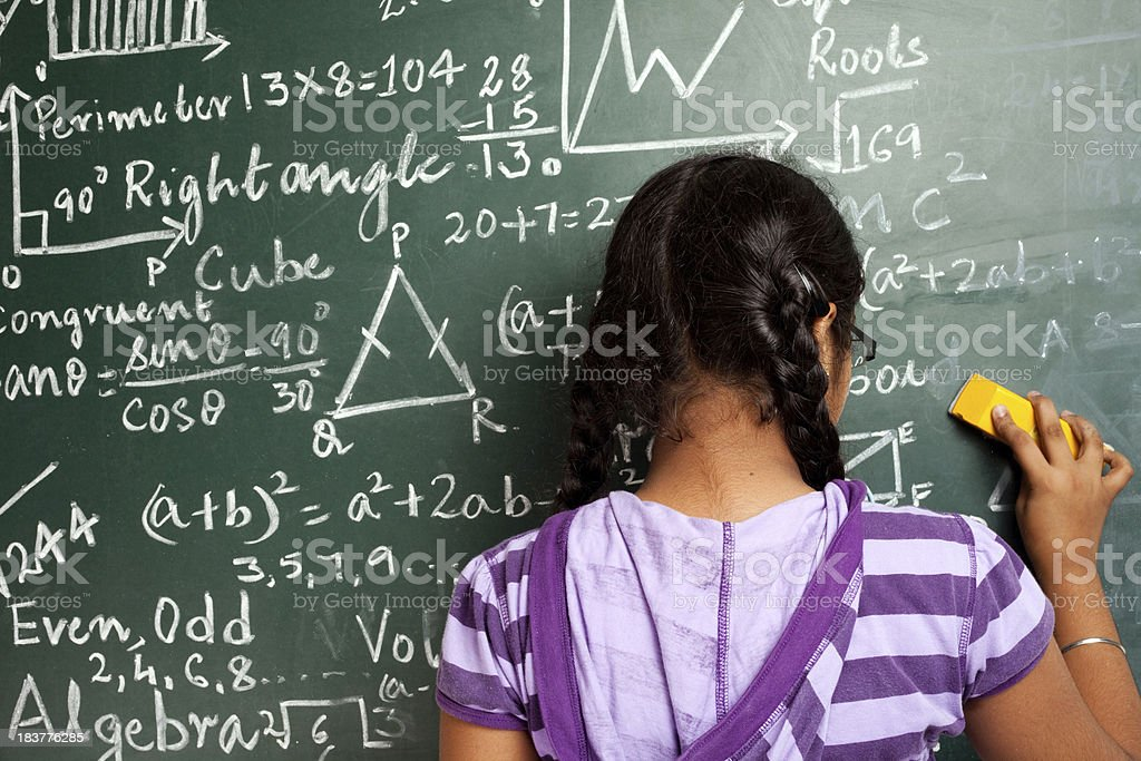 Indian Girl Student Erasing Mathematics Problems from Greenboard Blackboard stock photo