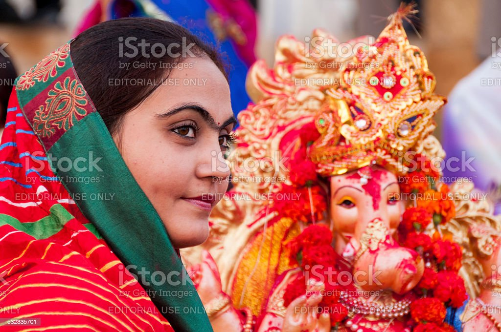 Indian girl watches  the statue of Lord Ganesha stock photo