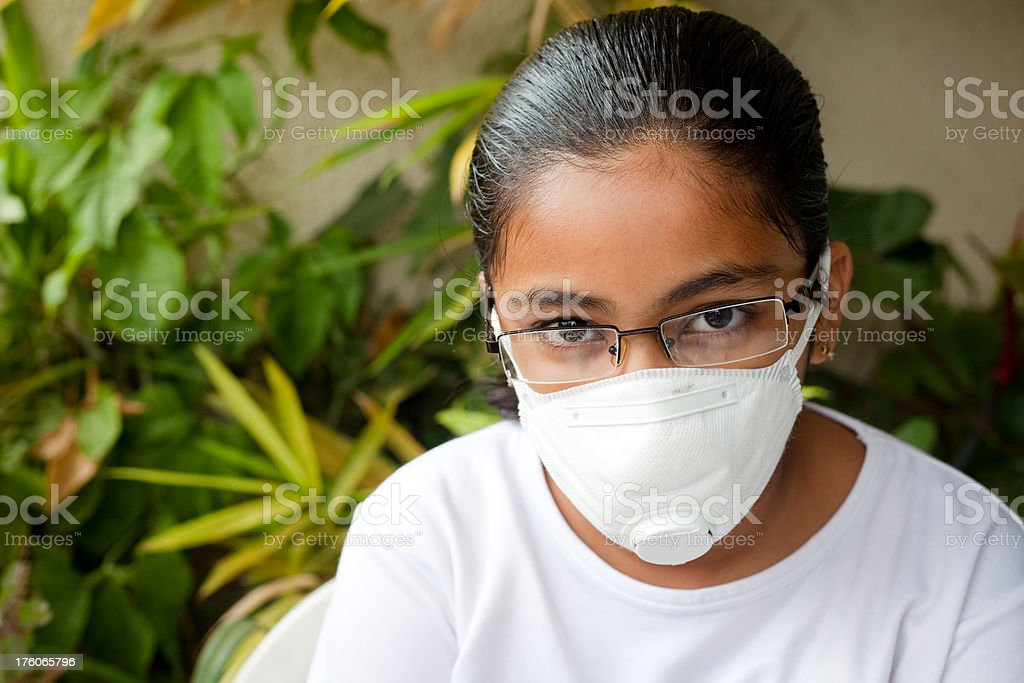 Indian girl wearing a mask against swine Flu stock photo