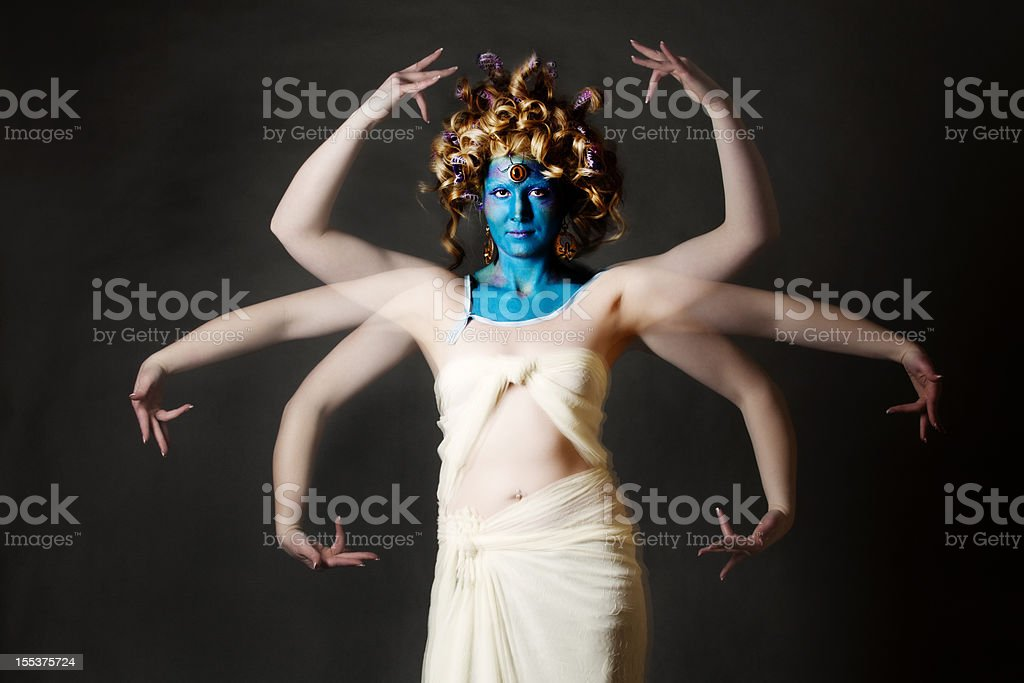 Indian goddess: blue-faced mystical creature with multiple arms stock photo