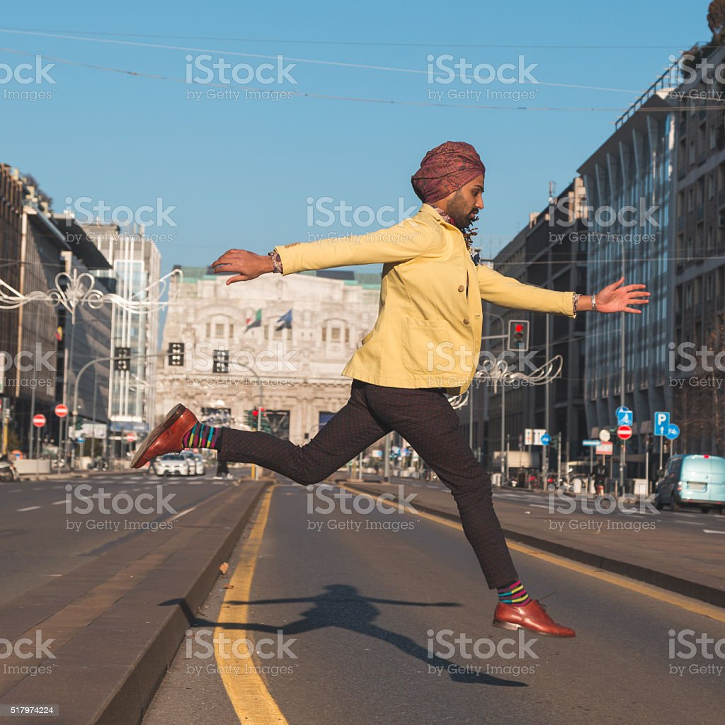Indian handsome man jumping in an urban context stock photo