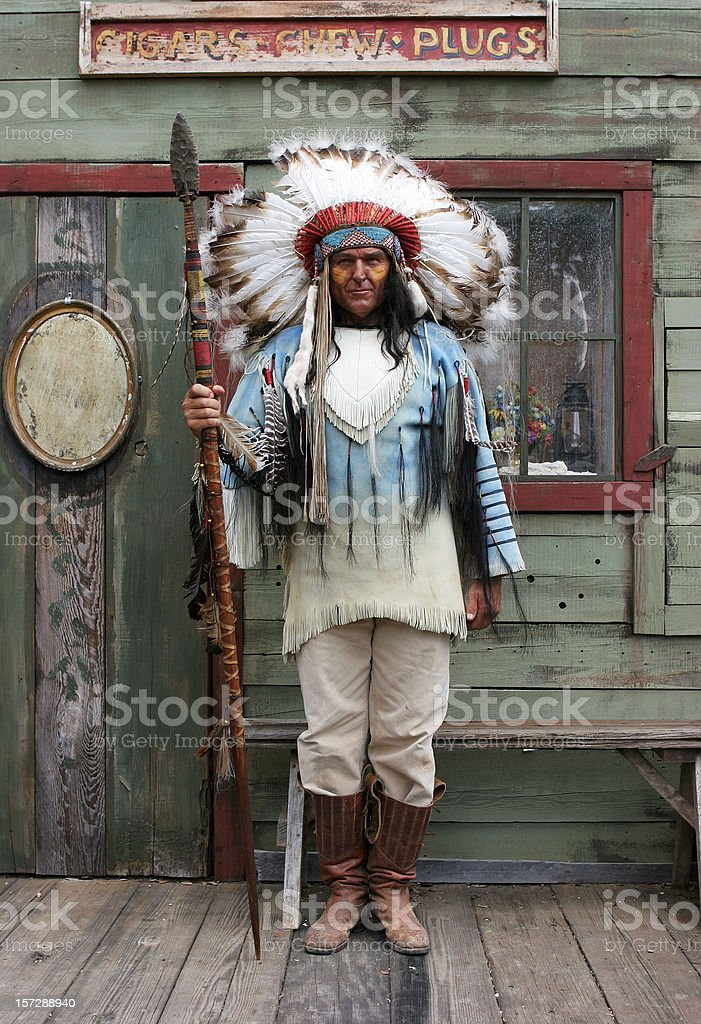 Indian holding spear in front of a wooden house stock photo