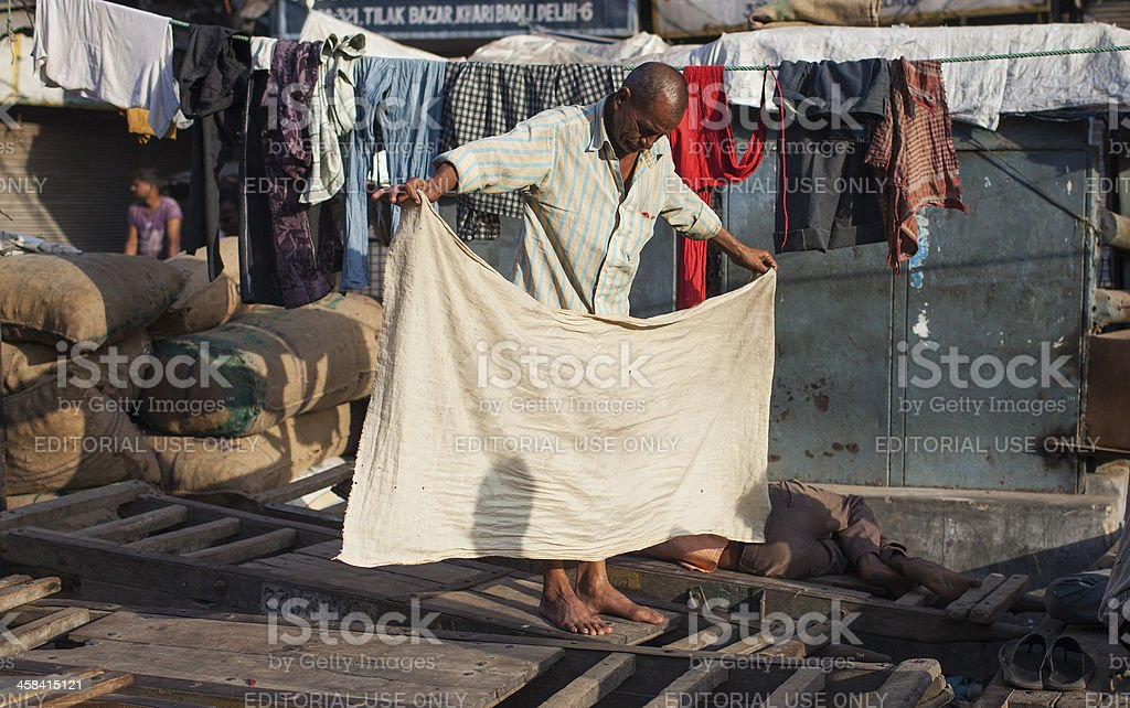 Indian labourer dries a sheet royalty-free stock photo