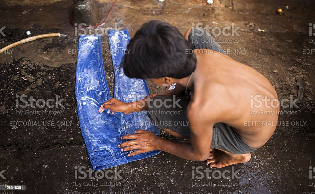Indian labourer washes jeans on road stock photo