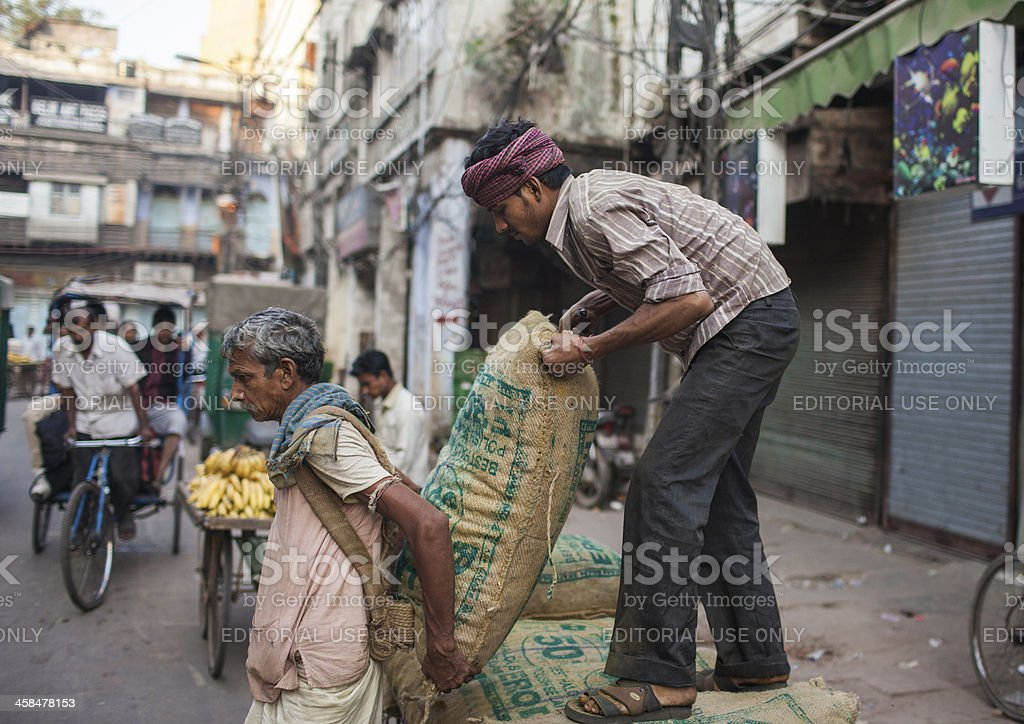 Indian labourers carry sacks stock photo