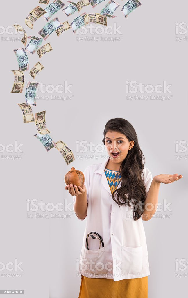 indian lady doctor and indian currency notes flying, saving concept stock photo