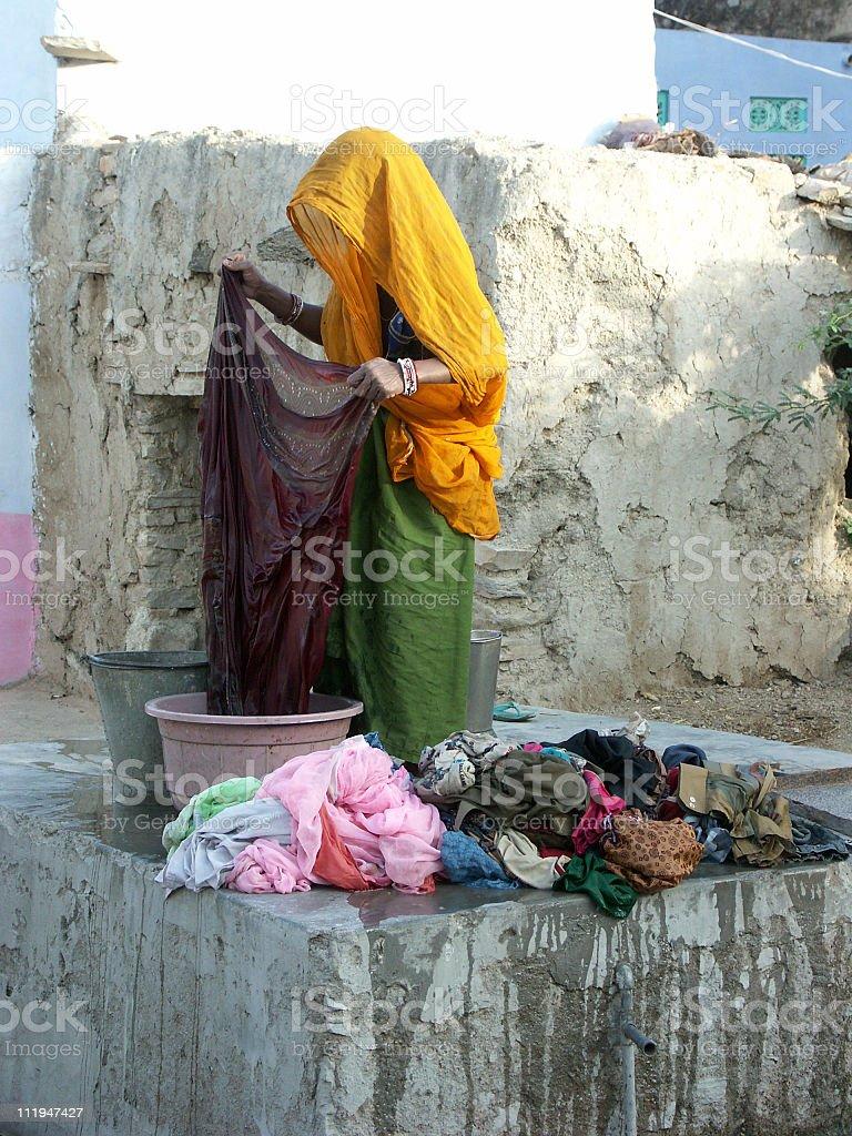 Indian lady washing clothes at waterpump, Rajasthan,India royalty-free stock photo