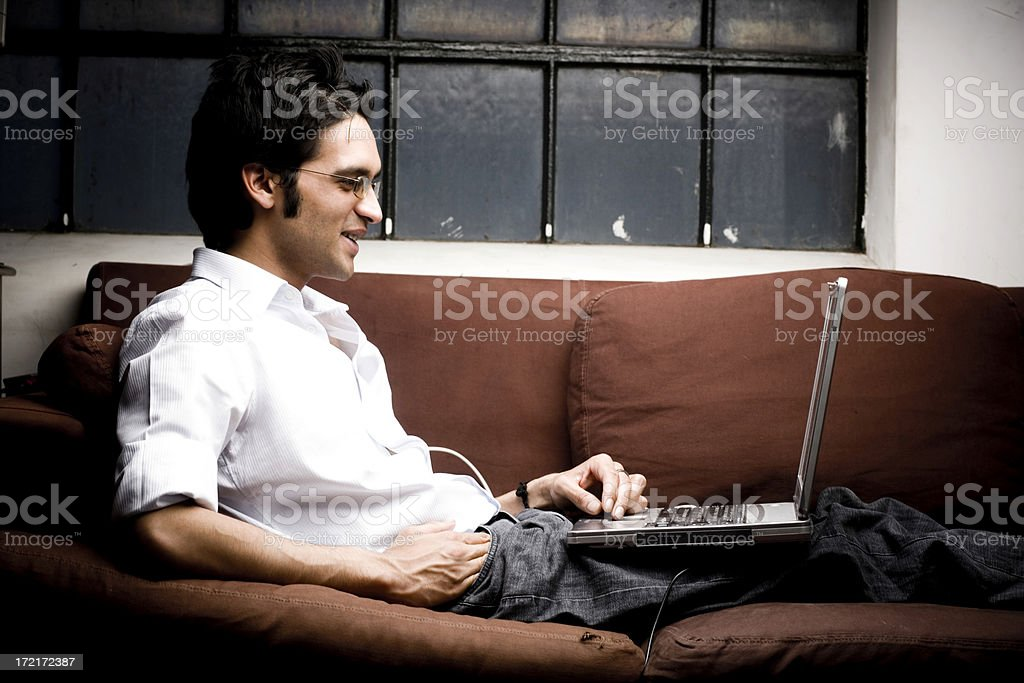 Indian Laptop Man working on sofa royalty-free stock photo