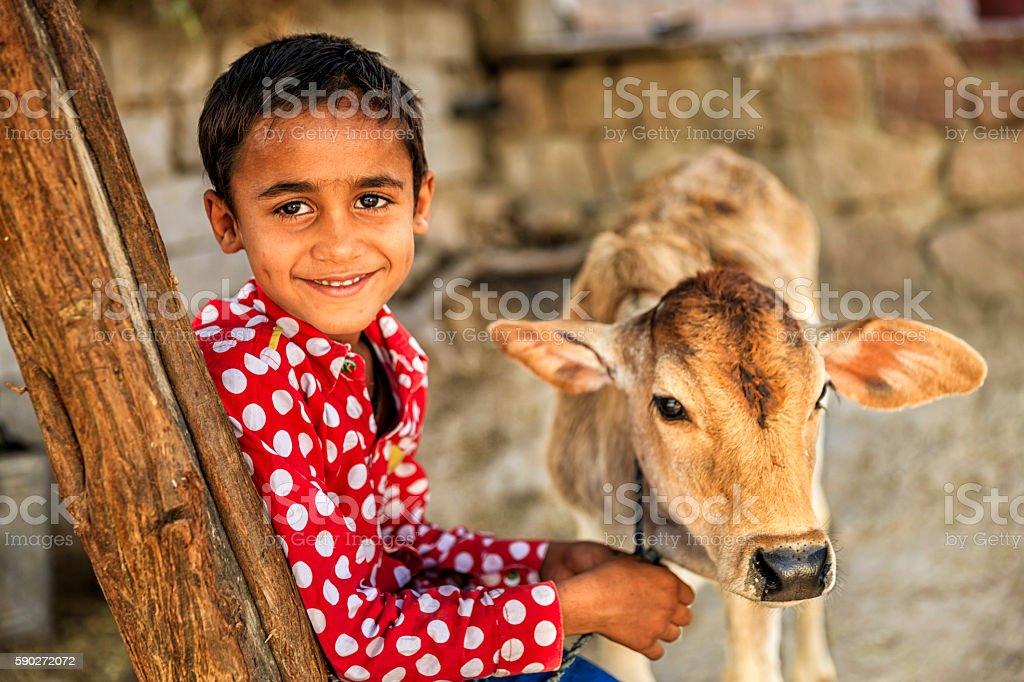 Indian little boy holding cow, Bishnoi village near Jodhpur, Rajasthan stock photo