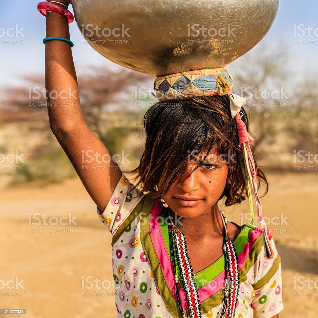 Indian little girl carrying on her head water from well stock photo