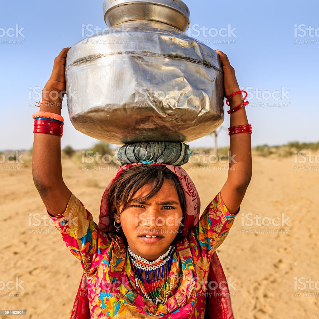 Indian little girl carrying on their heads water from well stock photo