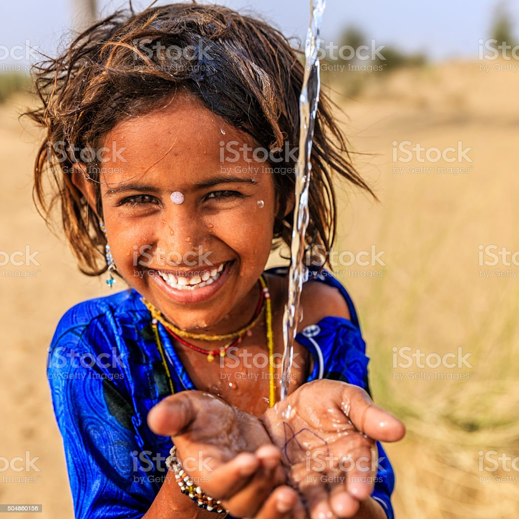 Indian little girl drinking fresh water, desert village, Rajasthan, India stock photo