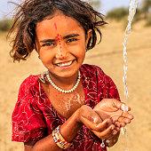 Indian little girl drinking fresh water, desert village, Rajasthan, India