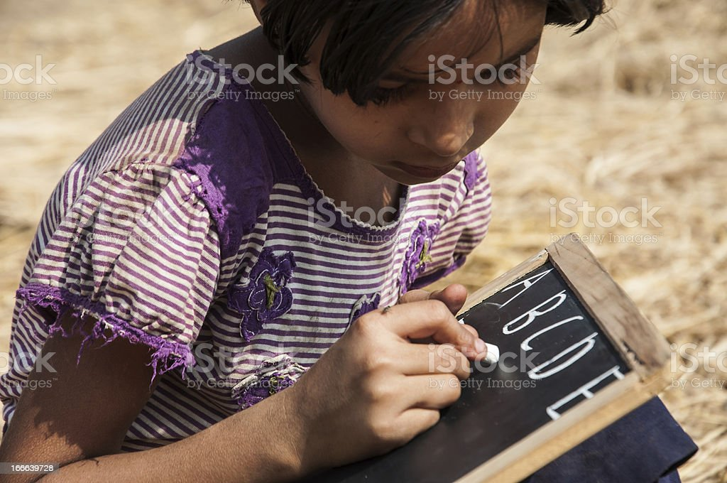 Indian little girl writing on slate stock photo